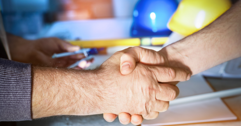 Construction worker shaking hand of newly hired employee